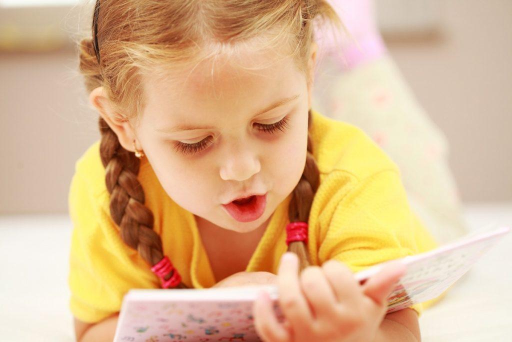 Liten jente som leser en bok