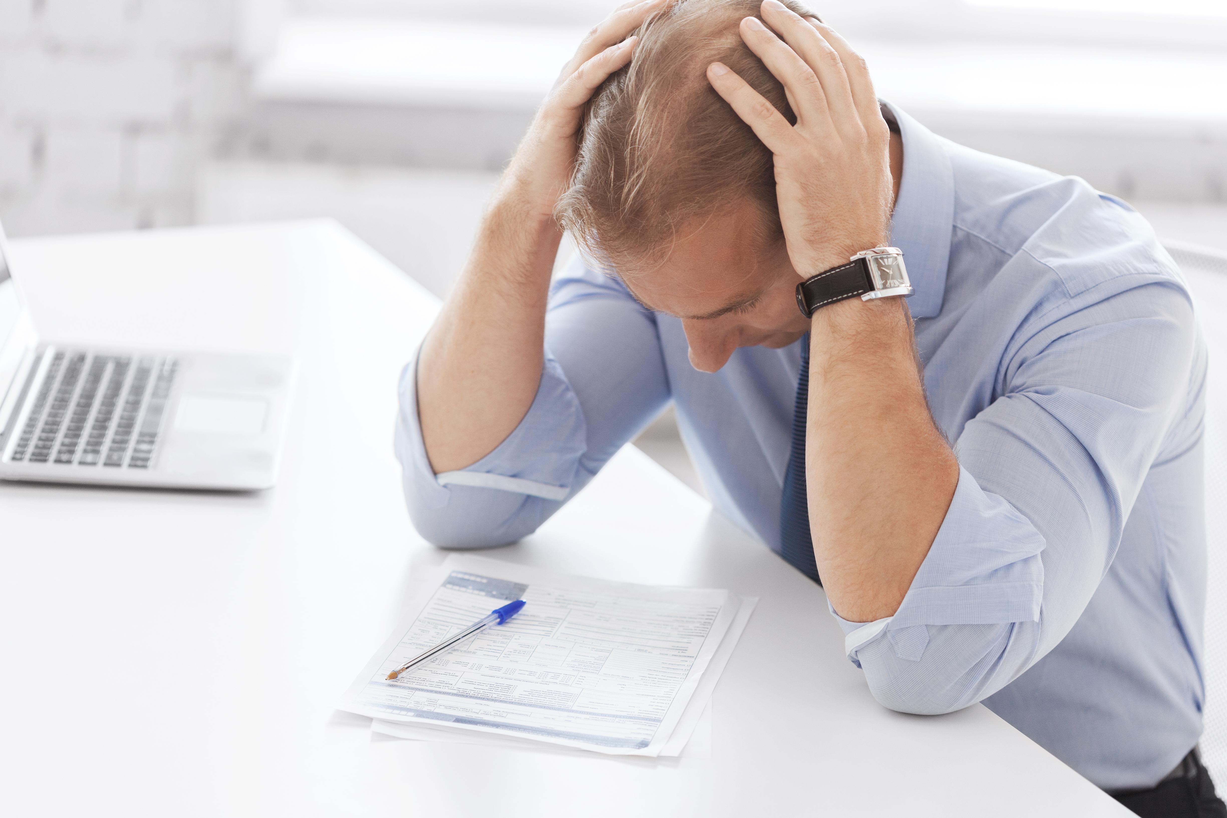 Stresset mann som holder seg på hodet med hendene ved skrivepult