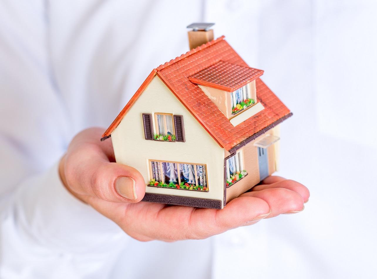 En hånd som holder et hus