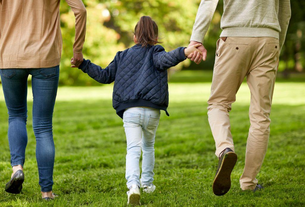Familie med mor og far og barn som holder hender og går tur i solen