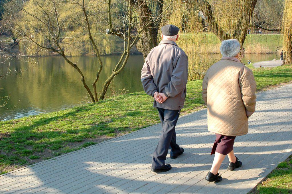 Eldre par går tur langs et vann